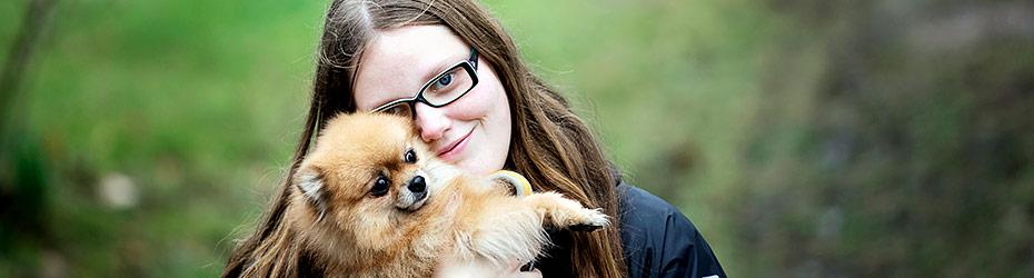 Nuori nainen ulkoilee koira sylissä