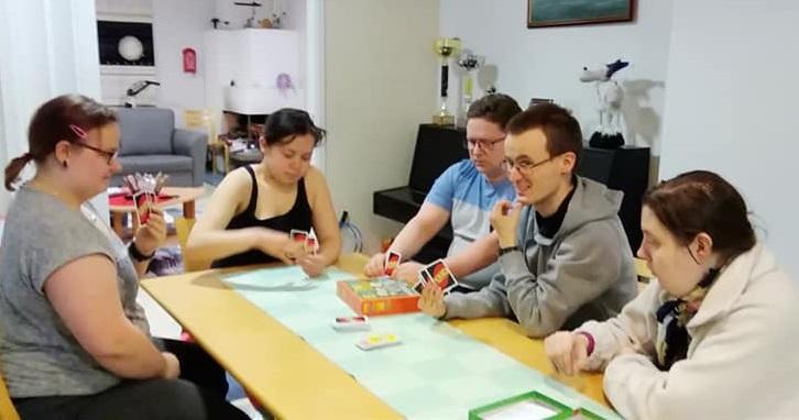 Viisi henkilöä pelaa Uno-korttipeliä pöydän ääressä.