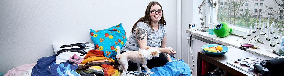 Nainen istuu sängyllä koiran vieressä