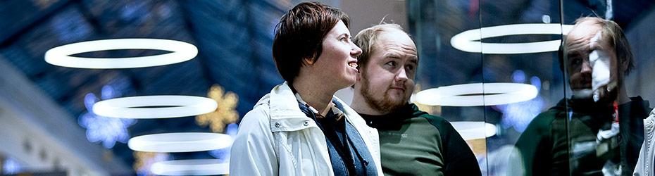 Nainen ja mies katsovat näyteikkunaa kauppakeskuksessa