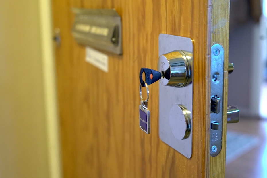 Kerrostaloasunnon ovi raollaan ja ovessa avain.