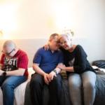 kolme henkilöä istuu hotellihuoneessa. Kaksi halaa, yksi katsoo kännykkää.