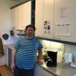 Mies kotonaan keittiötason luona.