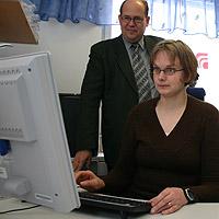 Nainen tietokoneen ääressä. Mies katsoo taustalta.