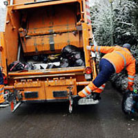 Mies ja oranssi jäteauto.