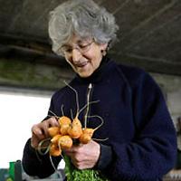 Nainen, jolla on kädessään pikkuporkkanoita.