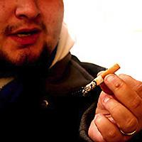 Mies pitelee tupakkaa kädessään.