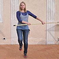 Nuori nainen voimistelee kepin avulla