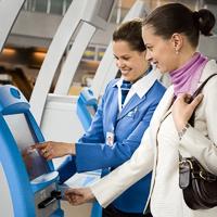 Lentokentän työntekijä auttaa matkustajaa käyttämään lähtöselvitysautomaattia.