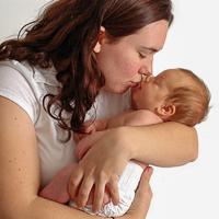 Äiti suukottaa vauvaansa.
