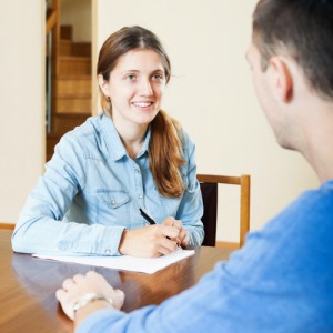 Handsome man an answer questions of social worker in home