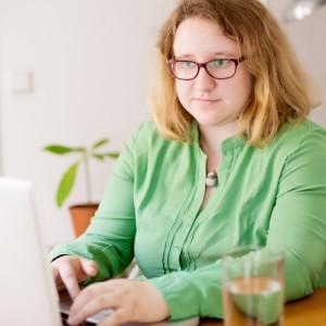 Nuori nainen istuu tietokoneen ääressä.