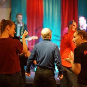 Yleisö tanssii bändin soittaessa taustalla.