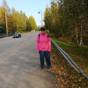 Pinkkiin takkiin pukeutunut nainen seisoo tienvieressä