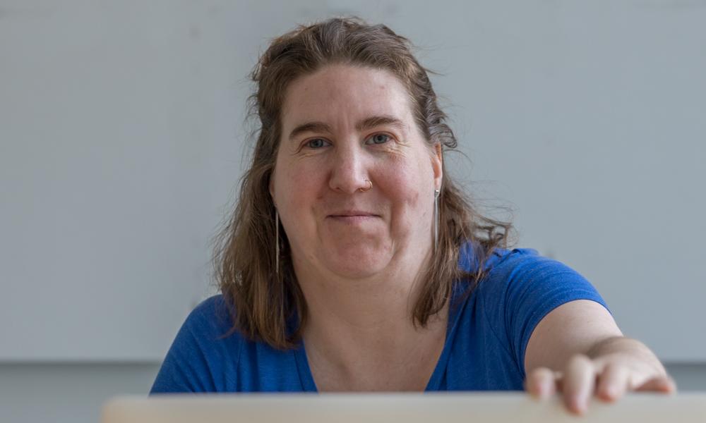 Kehitysvammainen nainen hymyilee tietokoneen äärellä