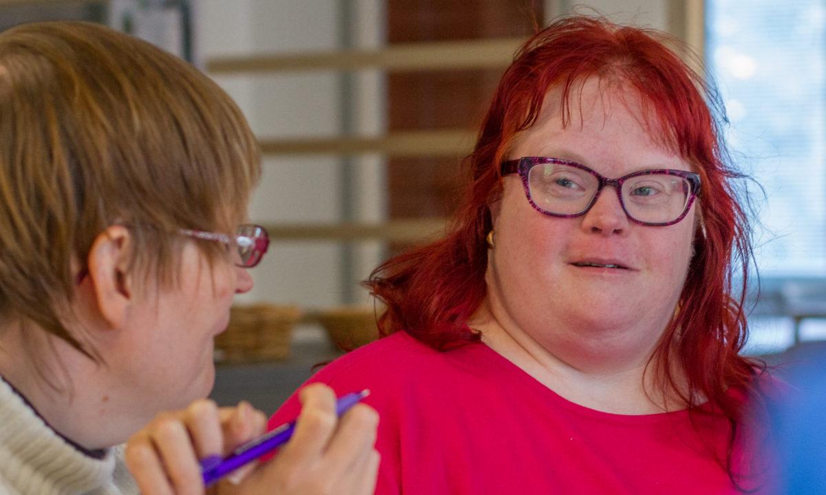 Kehitysvammainen nainen hymyilee kokouksessa