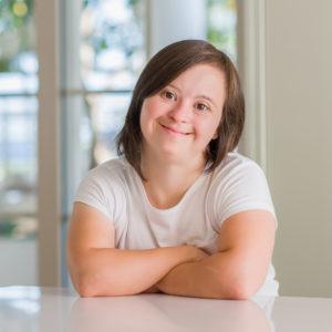 Nuori nainen hymyilee pöydän ääressä.