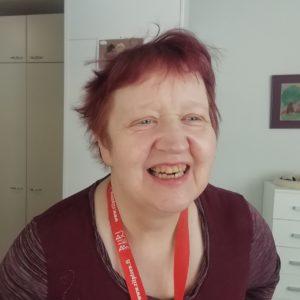 Lyhythiuksinen nainen nauraa iloisesti.
