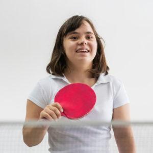 Nuori nainen pelaa pingistä ja nauraa.