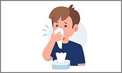 Nuori mies aivastaa nenäliinaan.