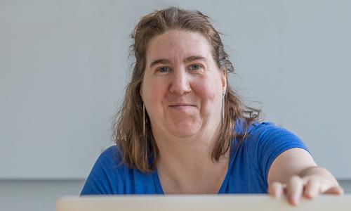 Kehitysvammainen nainen hymyilee tietokoneen takaa