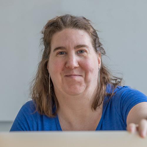 Nainen hymyilee tietokoneen takaa.