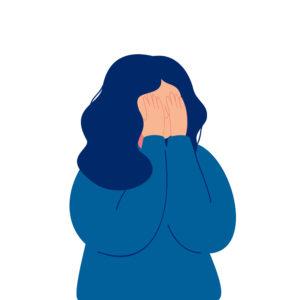 Nainen peittää kasvot käsillään.