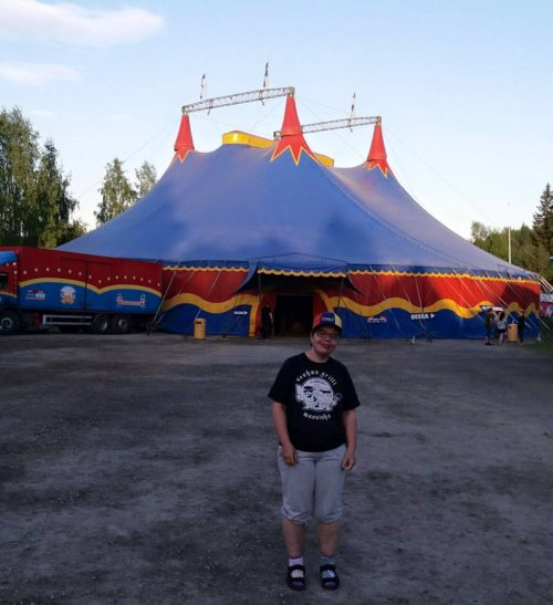 Nainen hymyilee sirkusteltan edessä.
