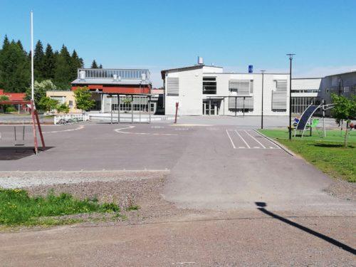 Valkoinen koulu ja koulun piha.
