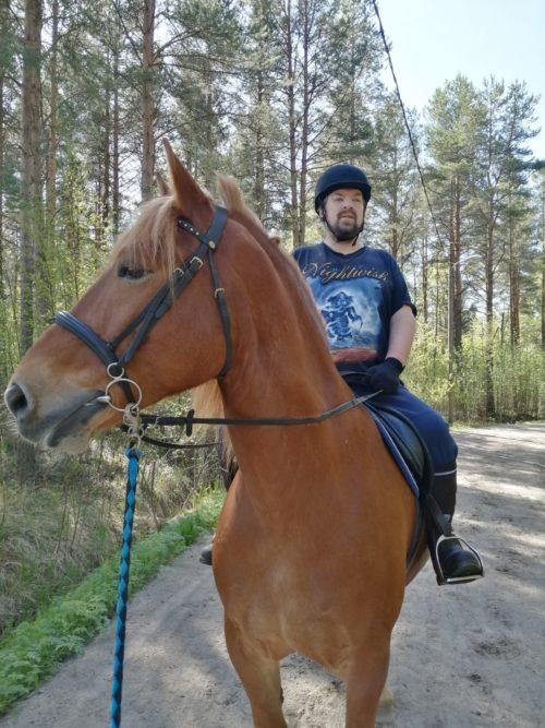 Mies istuu hevosen selässä maastossa