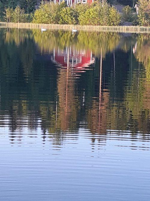 Veden pintaan heijastuu rannan punainen mökki.