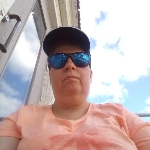 Nainen katsoo kameraan aurinkolasit päässä.