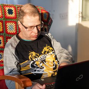 Mies käyttää kannettavaa tietokonetta.