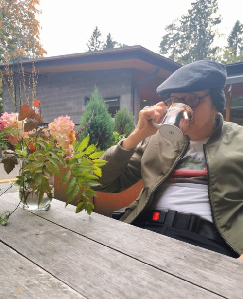 Mies istuu pihapöydän ääressä juomassa kahvia.