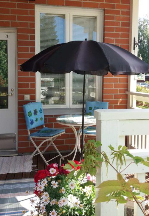 Terassilla auringon varjo, siniset tuolit ja kukkia.