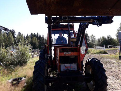 Mies ajaa traktoria pellolla.