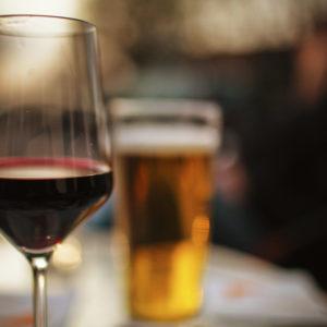Viinilasi ja tuoppi olutta.