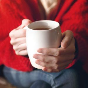 Nainen pitää kahvikuppia kädessään.