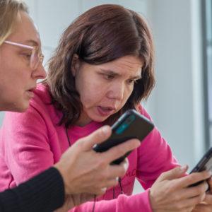 Nuori nainen käyttää kännykkää yhdessä ystävän kanssa.