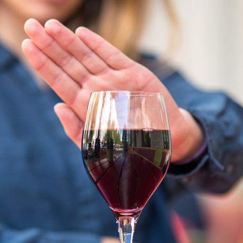 Nainen näyttää kädellä ei viinilasilliselle.