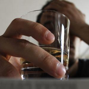 Nuori mies pitelee päätään ja toisessa kädessä lasia, jossa alkoholia.