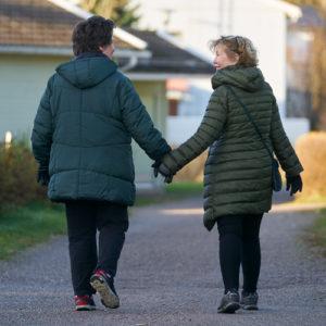 Kaksi naista kävelevät ulkona käsikädessä.