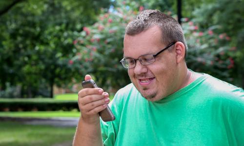 Kehitysvammainen mies katsoo kännykkää