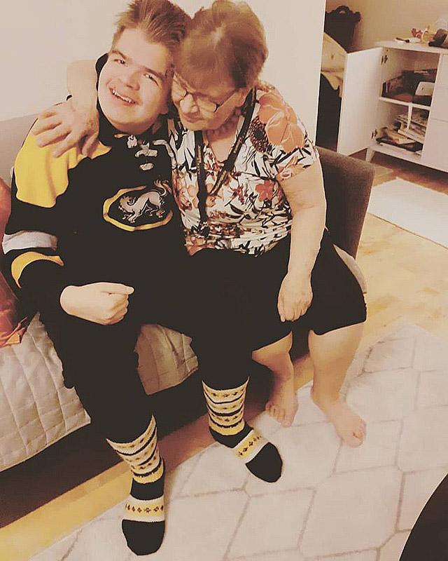 Uuno ja mummo halaavat. Uunolla on jalassaan mummon kutomat villasukat, joissa on Kärpät-joukkueen värit.