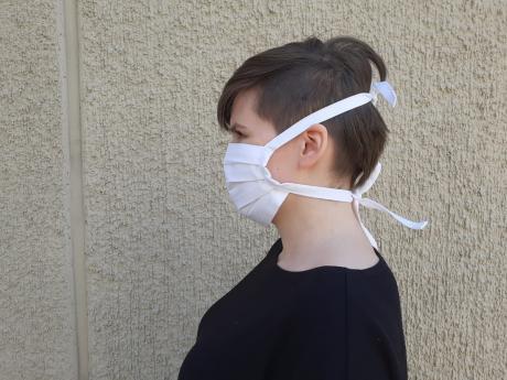 nainen, jolla on päässään Väylä Ry:ssä valmistettu kasvomaski