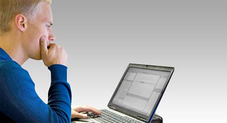 Mies istuu tietokoneen äärellä.