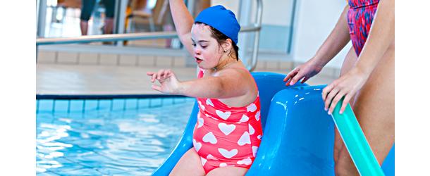 Kehitysvammainen tyttö on uimahallissa ja laskee liukumäkeä